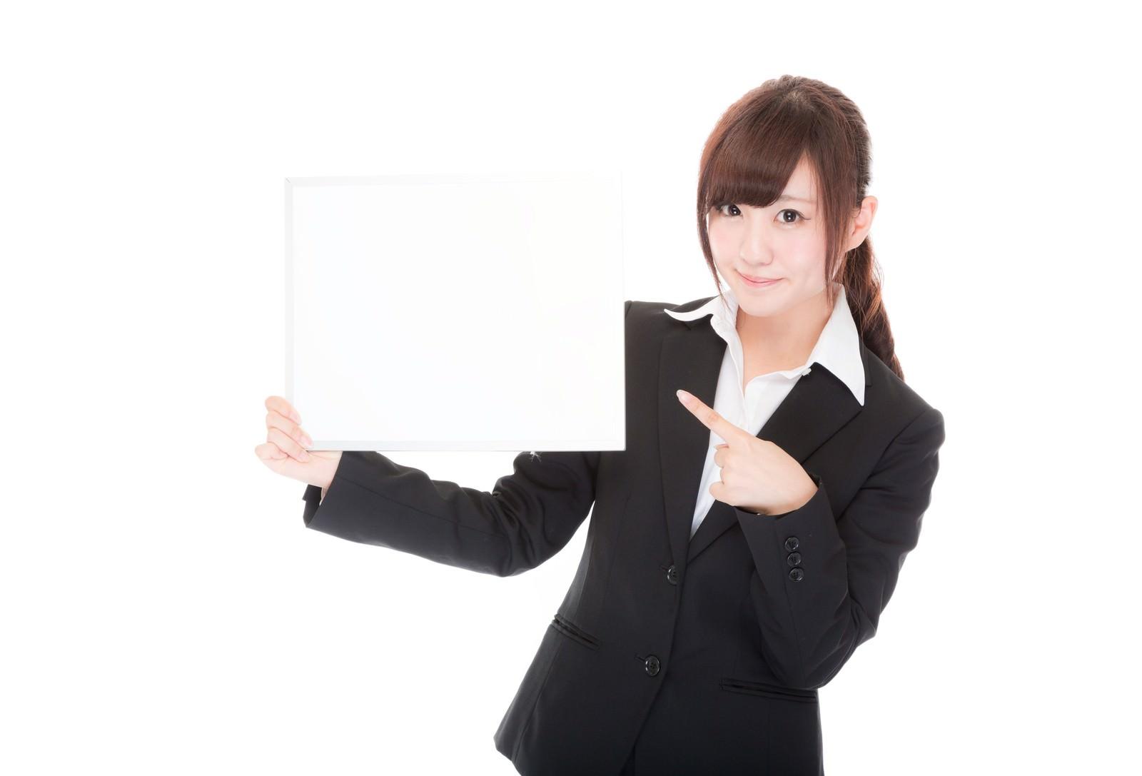 「白いボードを持って指をさすインフォメーション係」の写真[モデル:河村友歌]