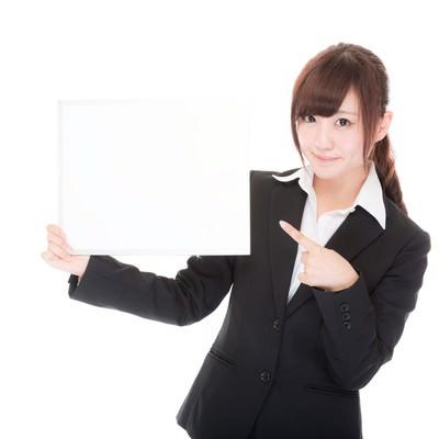 「白いボードを持って指をさすインフォメーション係」の写真素材