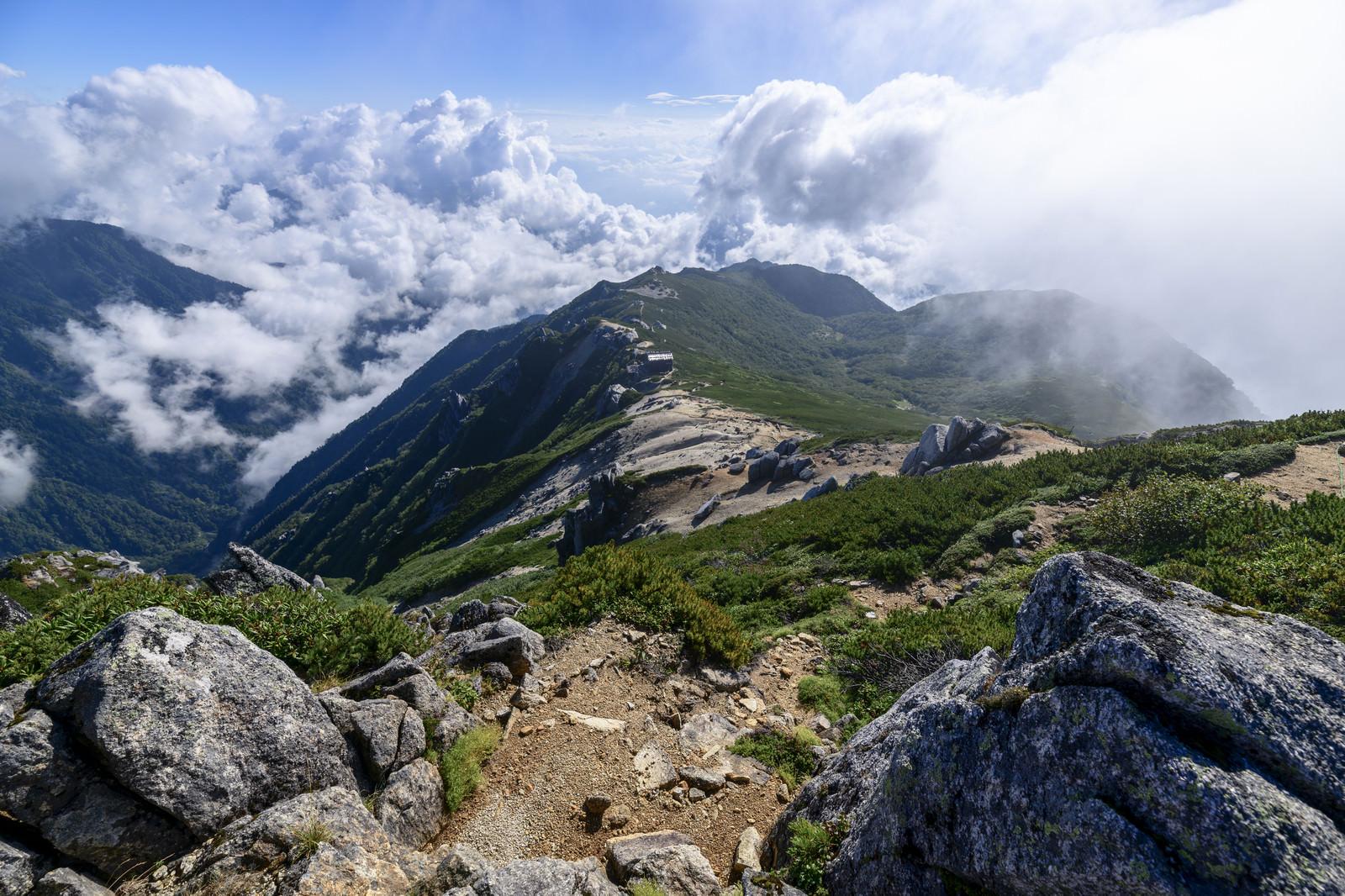 「巨大な雲が迫りくる駒峰ヒュッテと稜線」の写真
