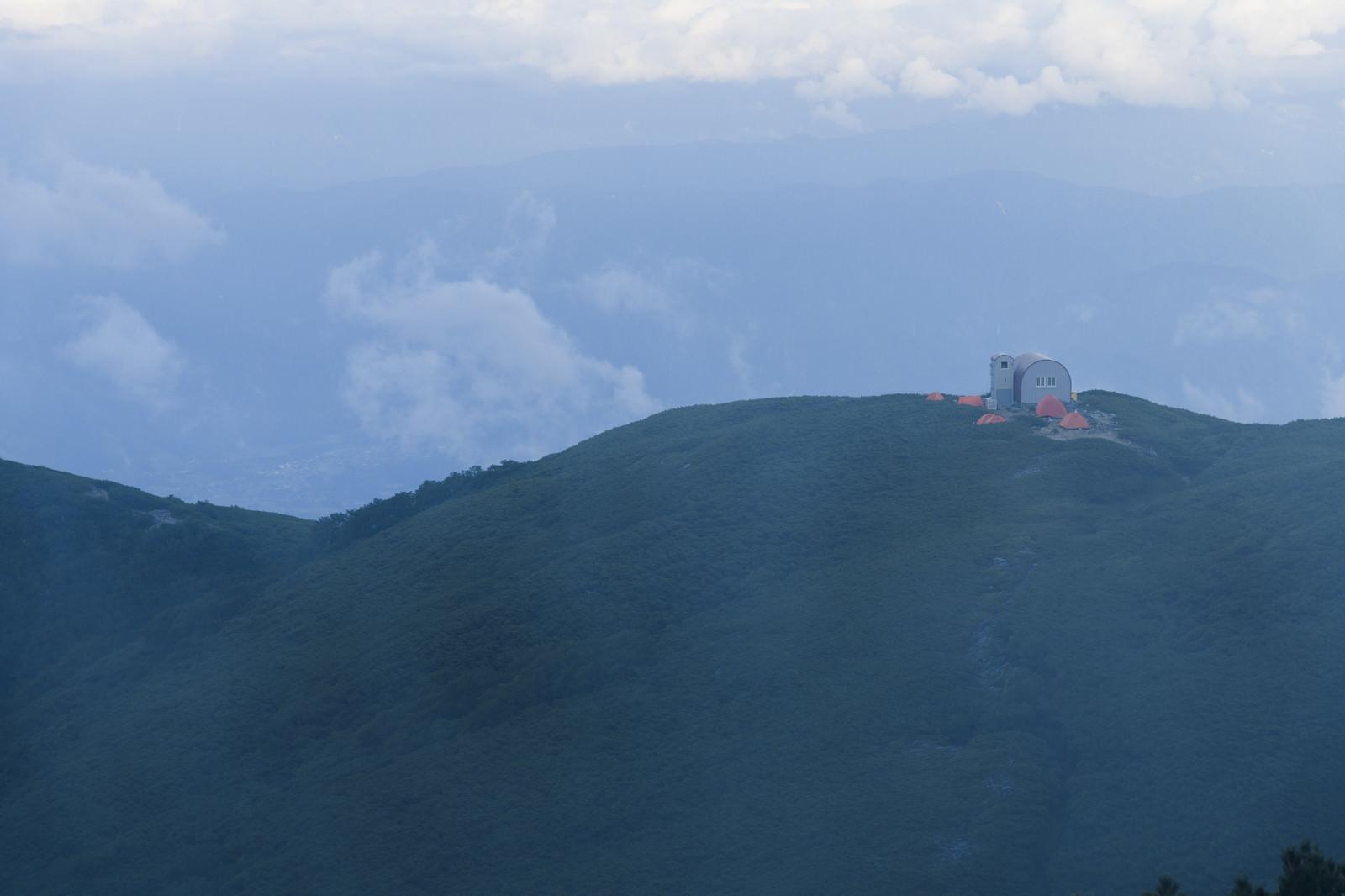 「霧の向こうに立つ檜尾岳の避難小屋」の写真