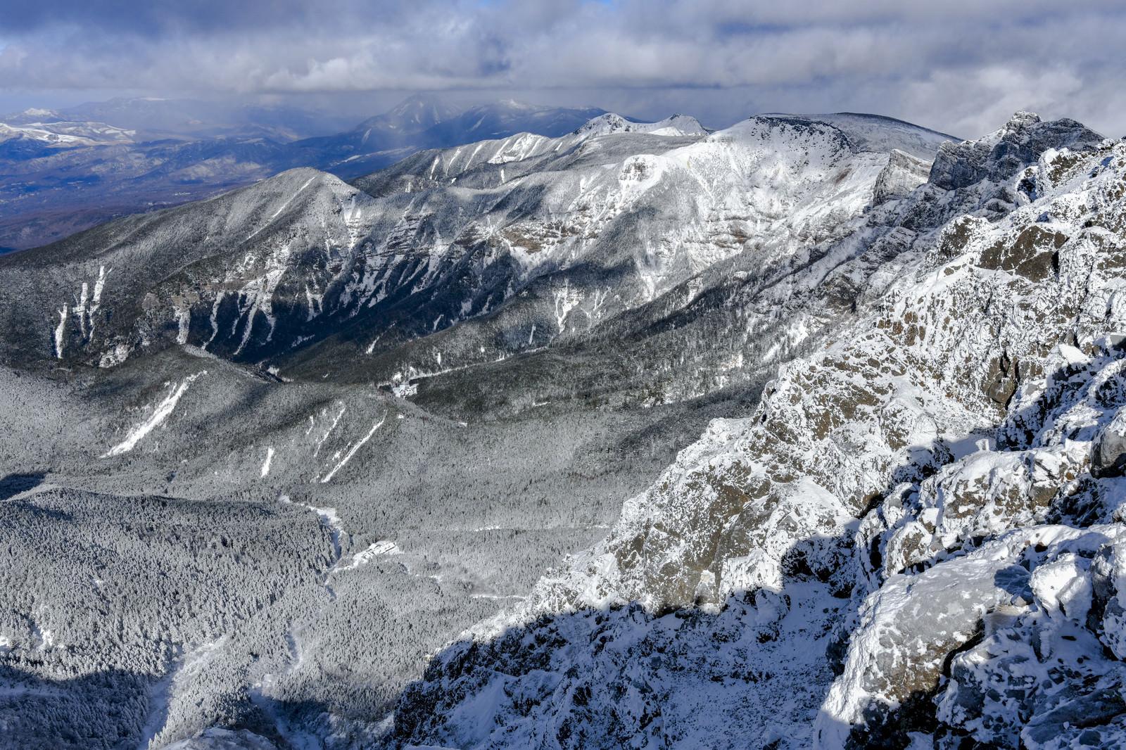 「雲に覆われゆく硫黄岳と八ヶ岳の白い森」の写真