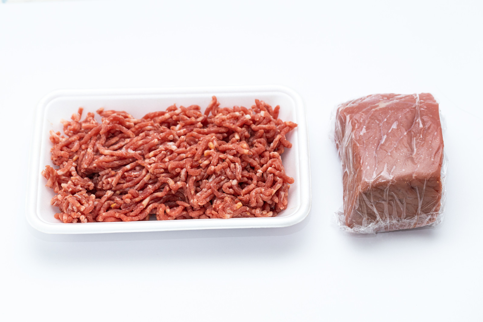 「合挽肉とラップに包まれたモモ肉(塊)」の写真