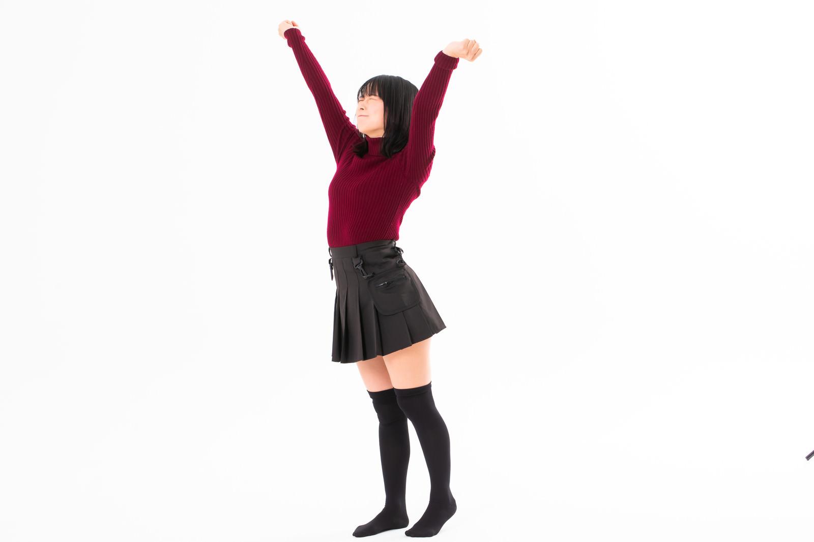 「両手を伸ばして背伸びする女性」の写真[モデル:にゃるる]