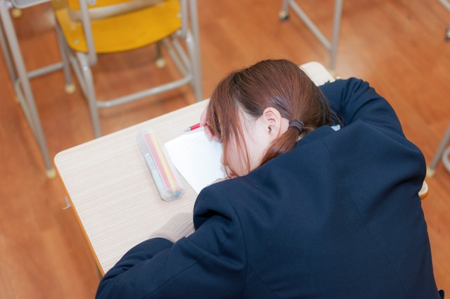 勉強中疲れて寝てしまった受験生の写真