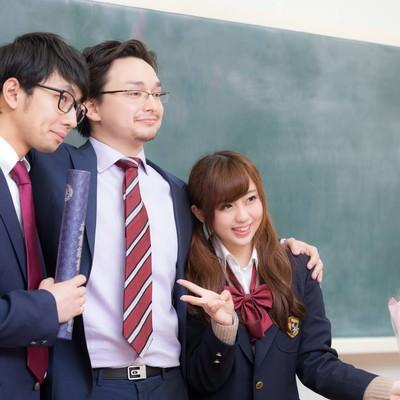 卒業式の後に記念撮影をする教師と教え子の写真