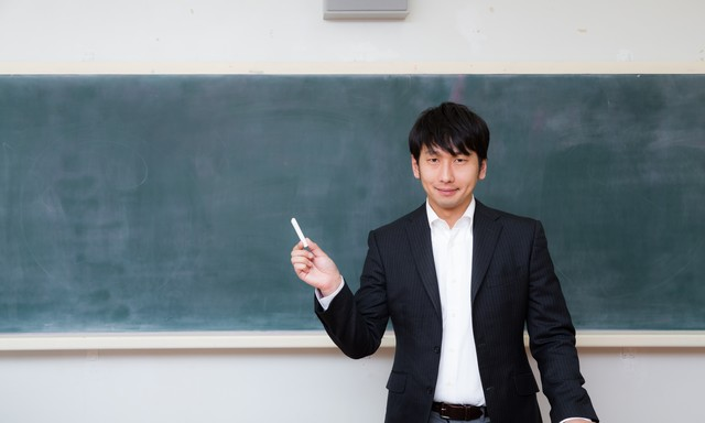 黒板の前で自己紹介をする新任教師の写真
