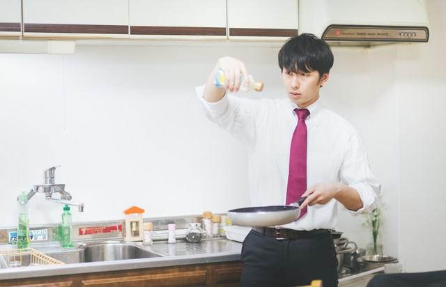 男の料理は高い位置からオリーブオイルをたらすの写真