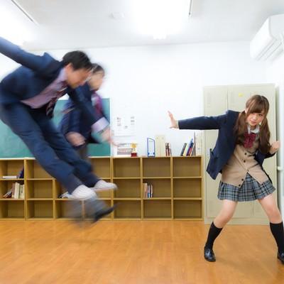 「片手で男性2人を投げ飛ばす女子高生」の写真素材