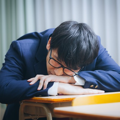 「補習中居眠りをする留年候補生」の写真素材