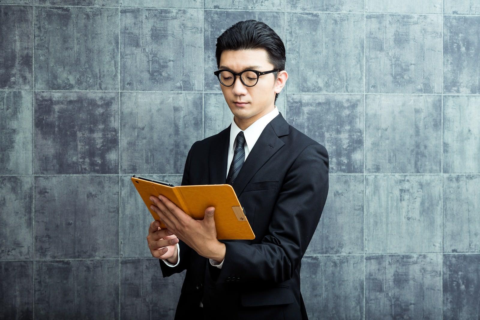 「名簿を確認する案内人」の写真[モデル:OZPA]