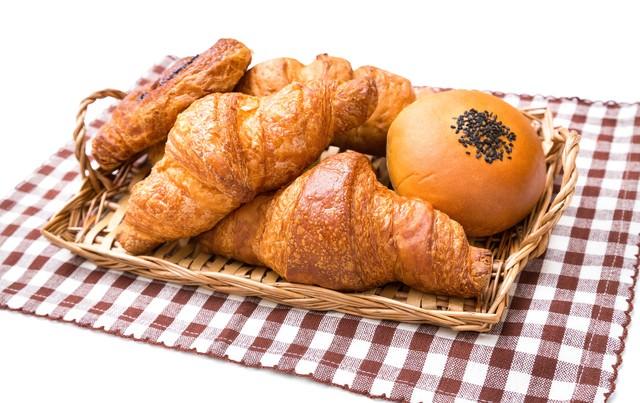 バスケットに山盛りのパン(クロワッサンなど)の写真