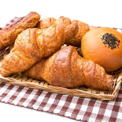 「バスケットに山盛りのパン(クロワッサンなど)」の写真素材