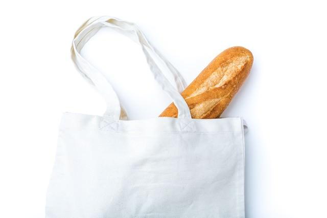 無地のトートバッグに入ったフランスパンの写真