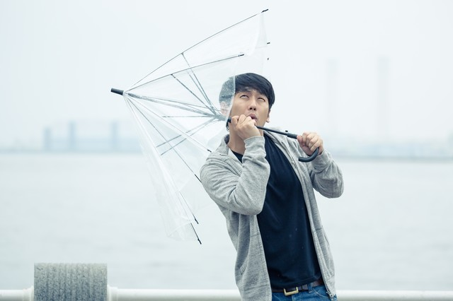 強風で傘が持っていかれそうになる男性の写真