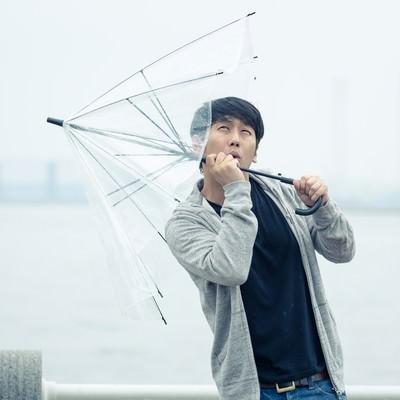 「強風で傘が持っていかれそうになる男性」の写真素材