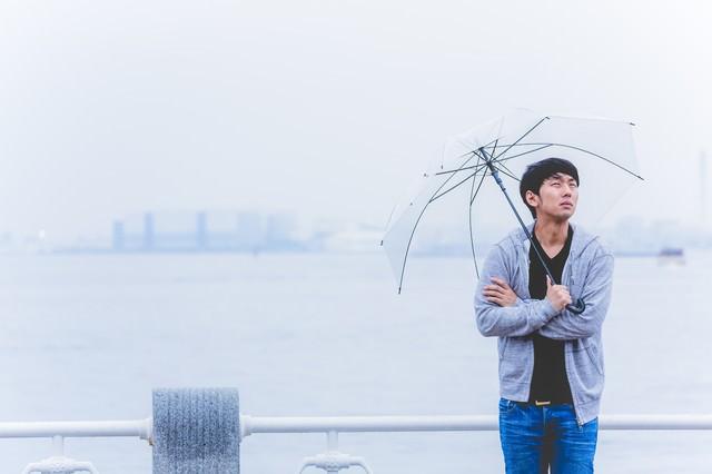雨の中、出番待ちの若手俳優の写真