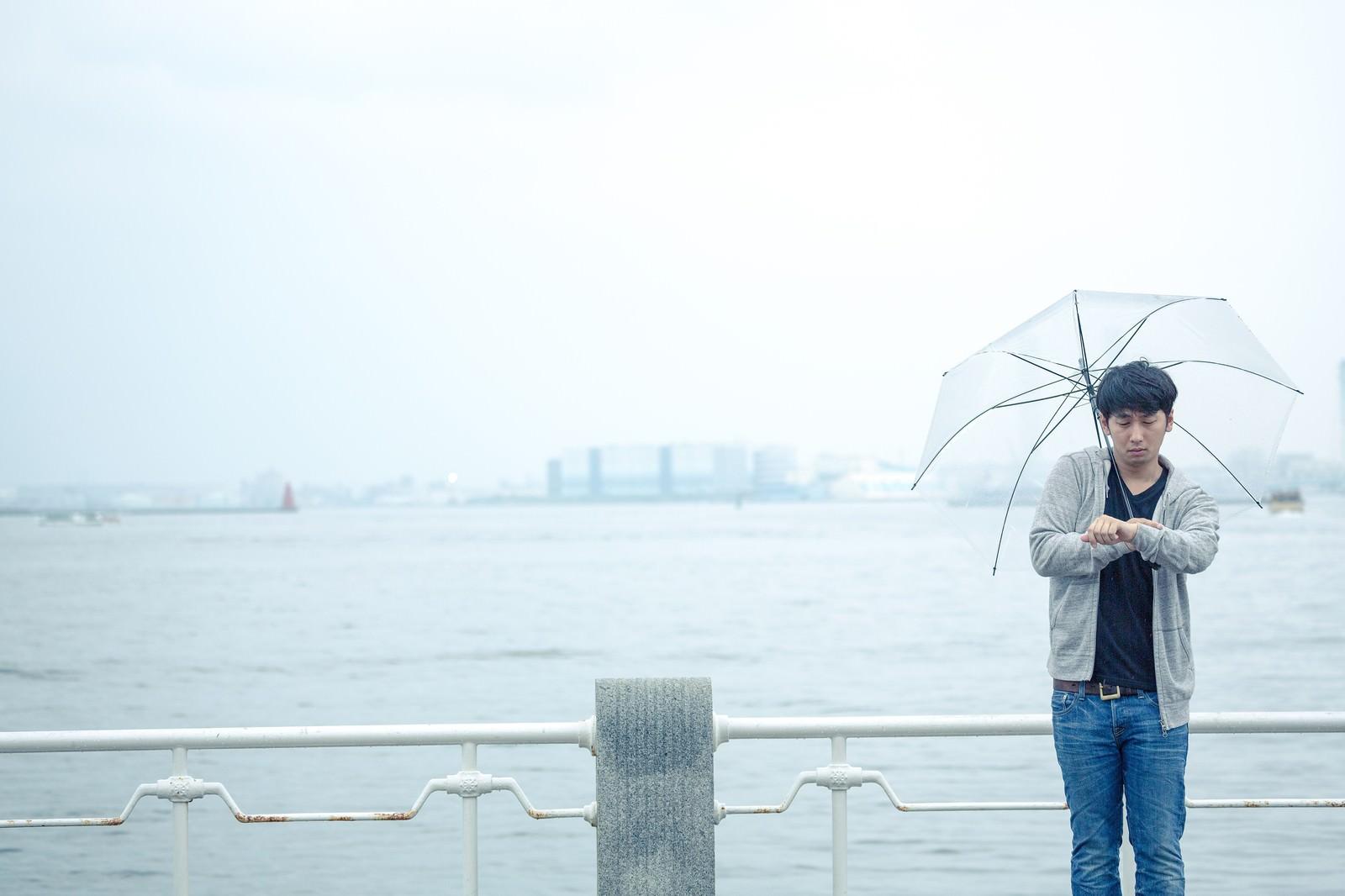 「雨の日の初デート、時間を確認するしぐさで高鳴りをごまかす男性」の写真[モデル:大川竜弥]