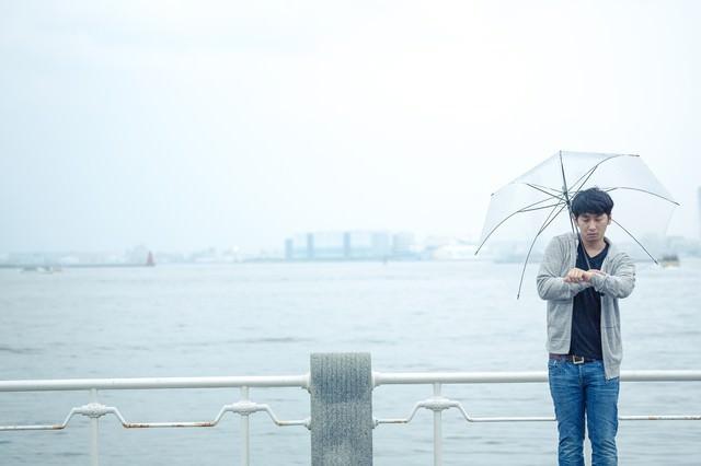 雨の日の初デート、時間を確認するしぐさで高鳴りをごまかす男性の写真