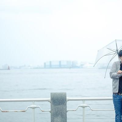 「雨の日の初デート、時間を確認するしぐさで高鳴りをごまかす男性」の写真素材