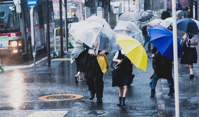 台風で突風が吹く駅前と必死に傘をさす人々