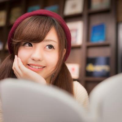 「マンガを読みながら続きを妄想する美少女」の写真素材