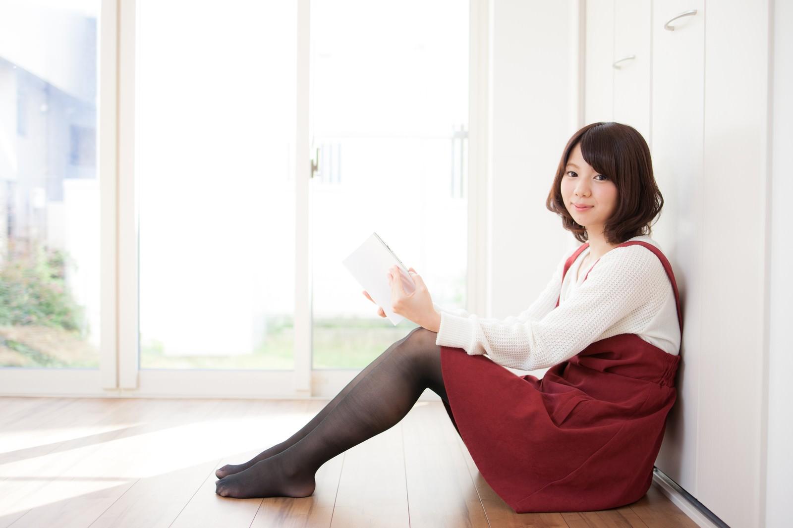 「陽が入るリビングで読書中の女性」の写真[モデル:みき。]