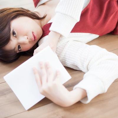 「フローリングに寝転び読書をする女性」の写真素材