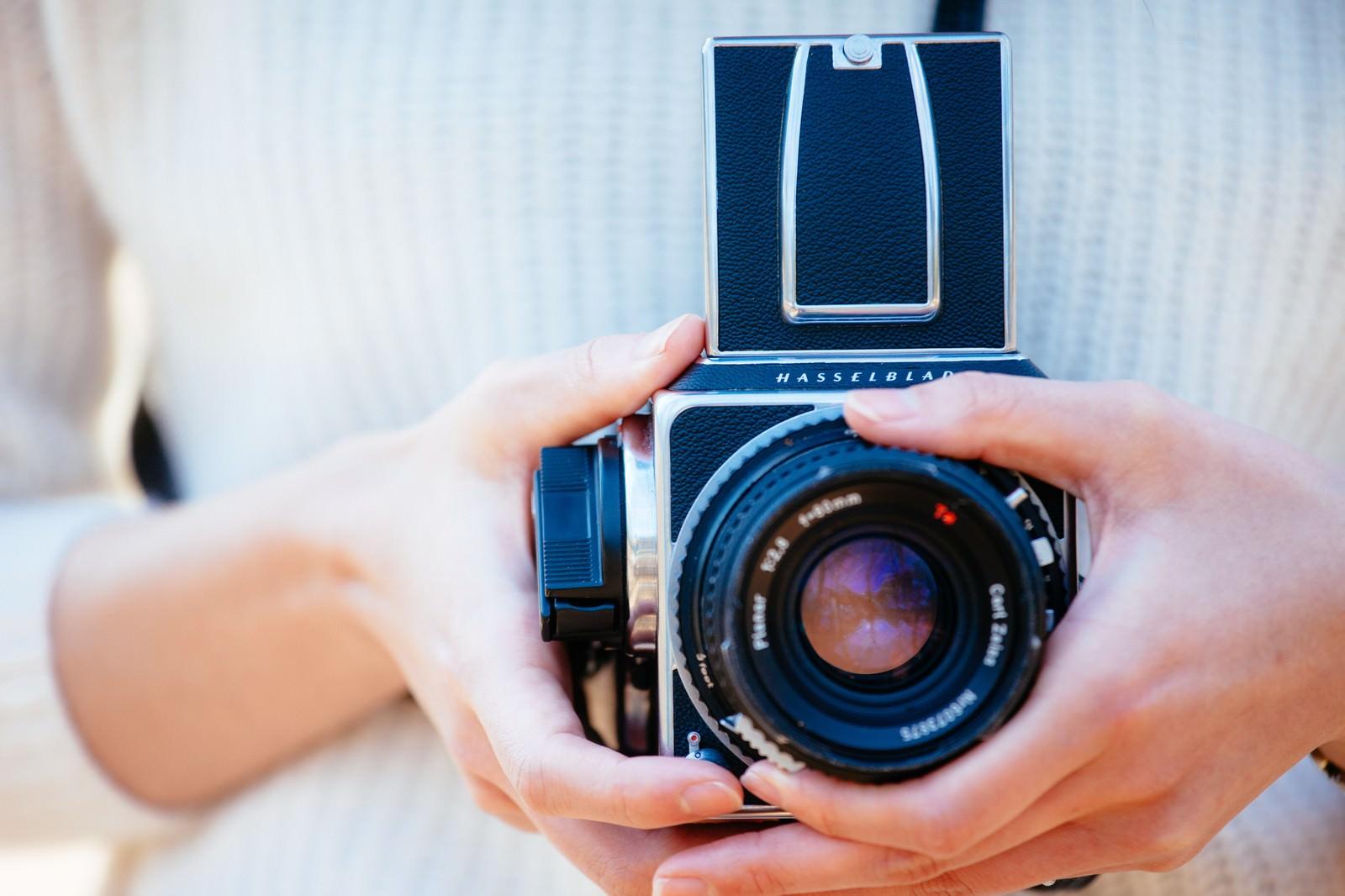 「フィルムカメラを持った女性の手」の写真