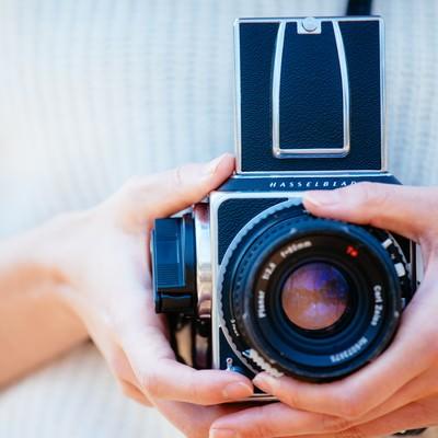 「フィルムカメラを持った女性の手」の写真素材