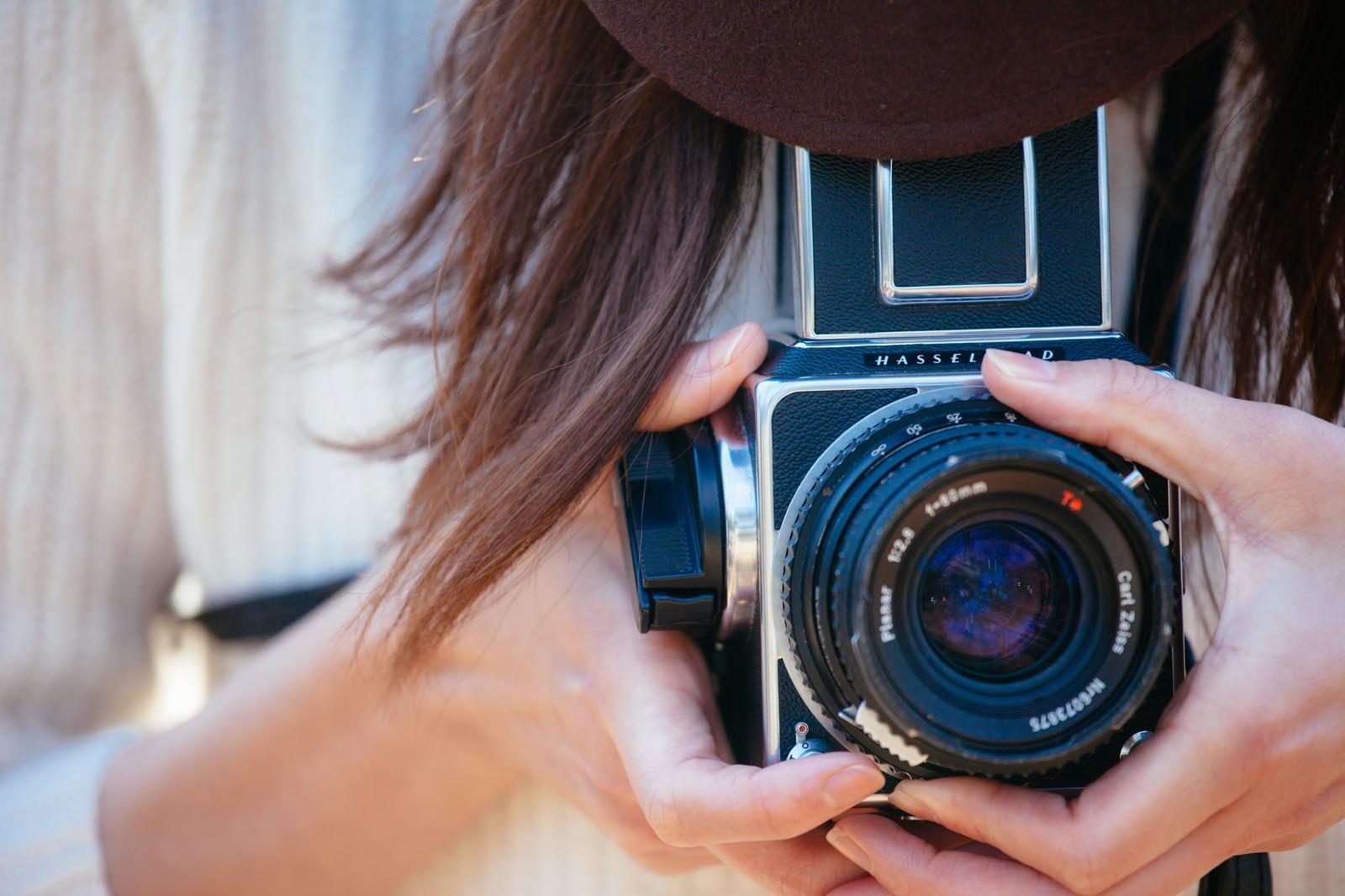 「フィルムカメラを持って撮影」の写真