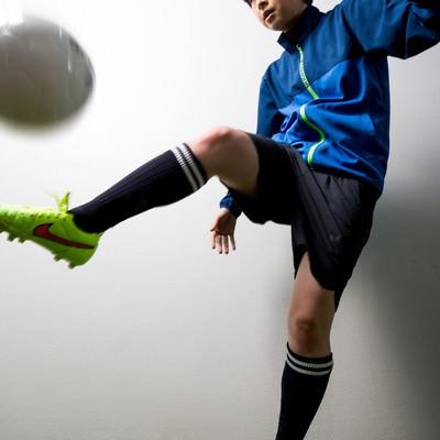 室内でサッカーボールをトラップする女性選手の写真