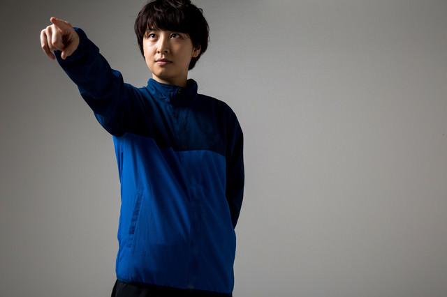 選手交代を伝える若い女性監督の写真