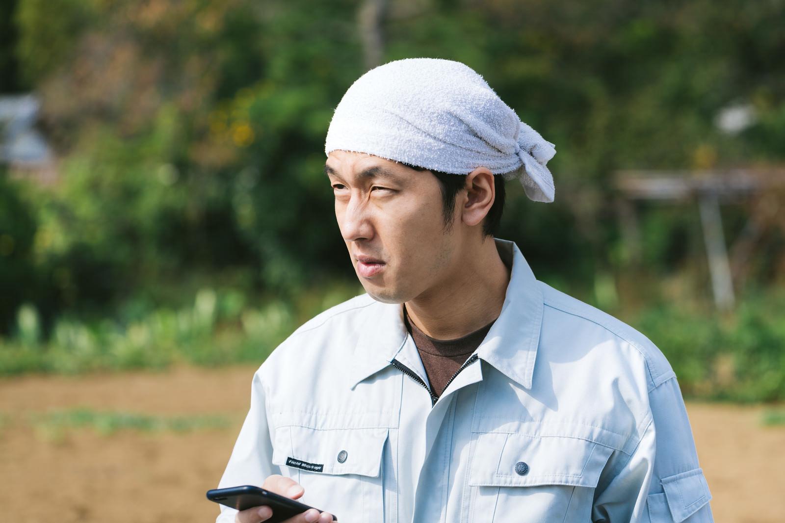 「「電波が入らねぇ…」と憤慨する元エンジニアの農民」の写真[モデル:大川竜弥]
