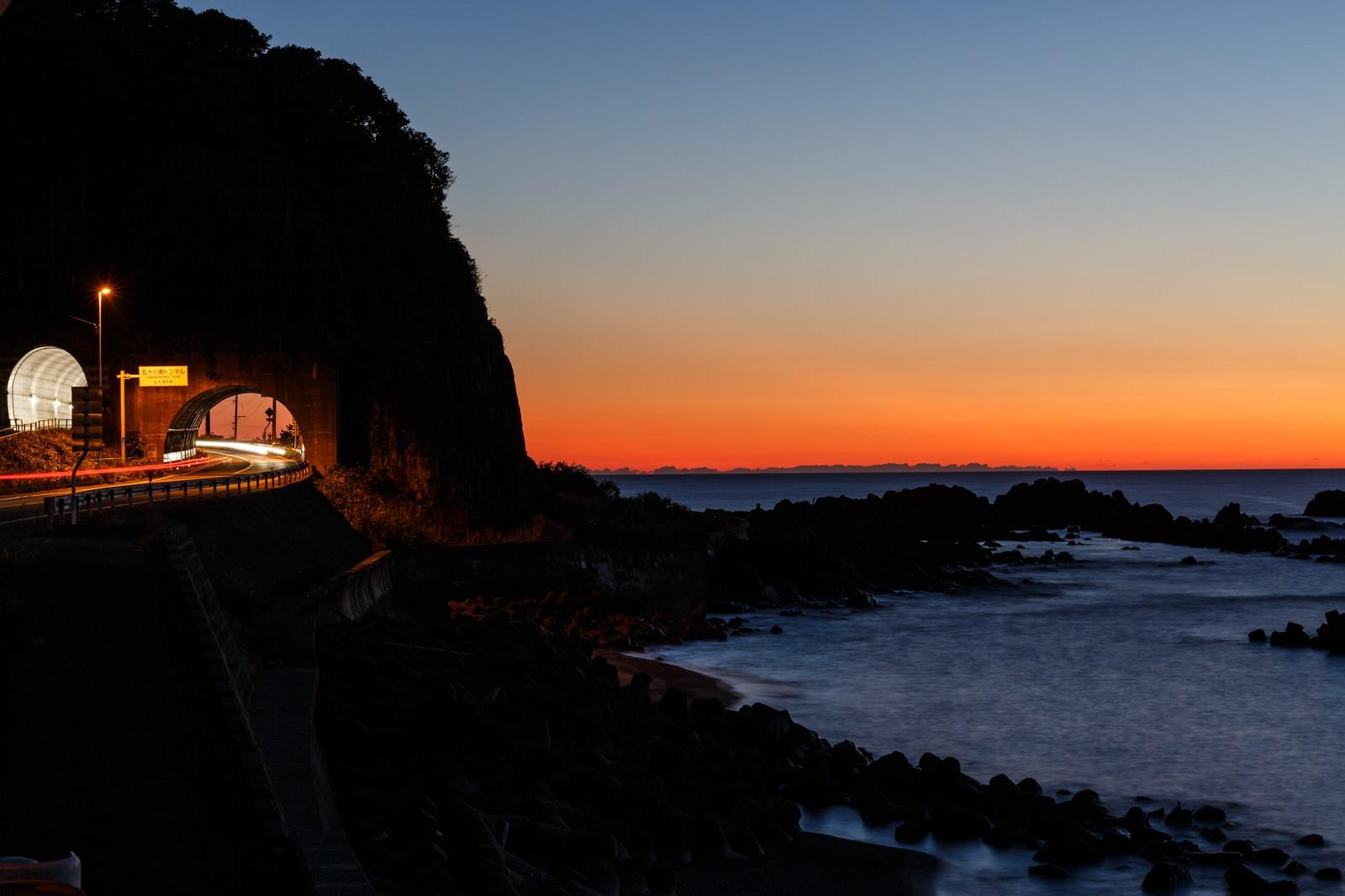 「日没の日本海と沿岸の道路」の写真