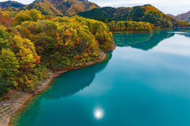 ダム湖に反射する太陽(紅葉時期)の写真
