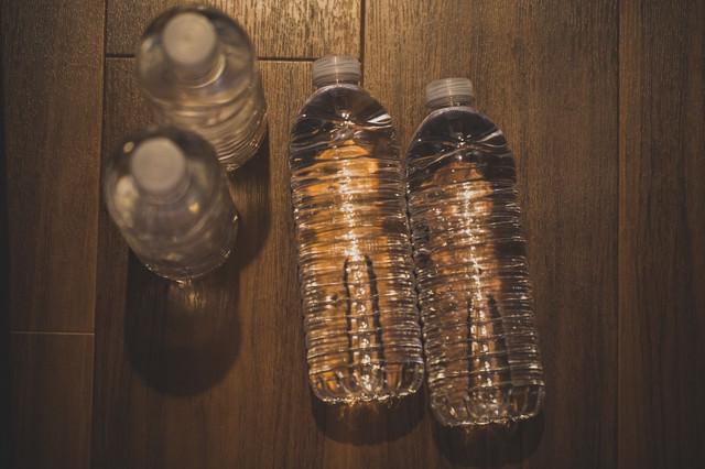 床に置かれた水のペットボトルの写真