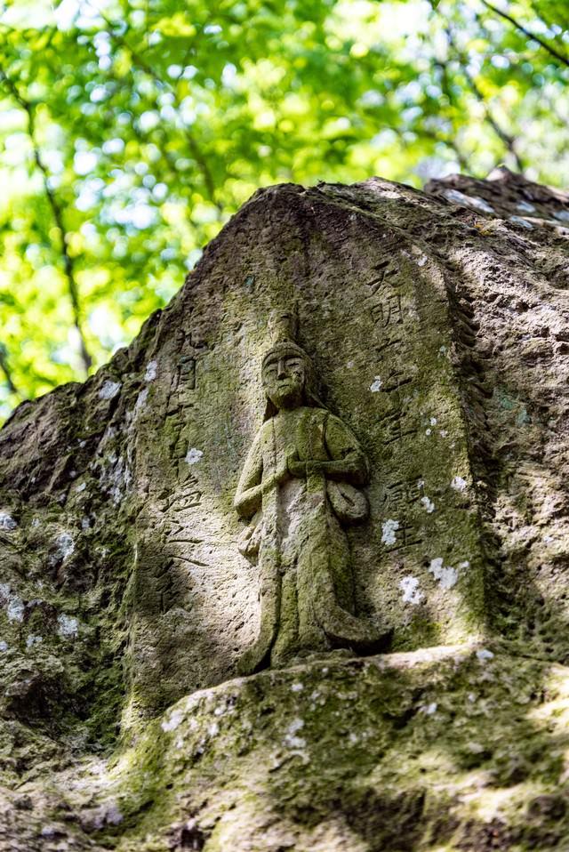 木漏れ日に包まれる石像(武石公園)の写真