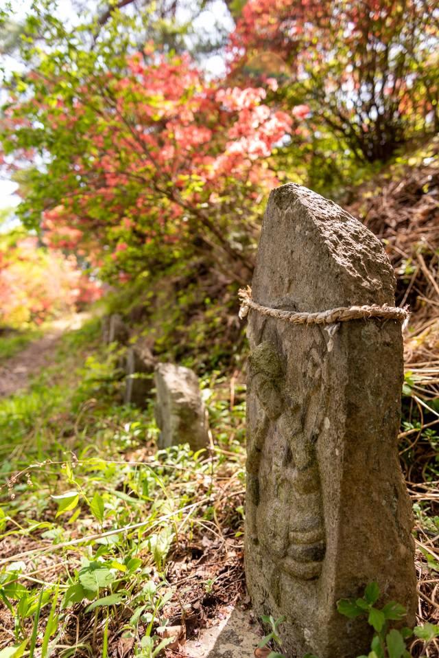 武石公園のツツジと道端の石像の写真