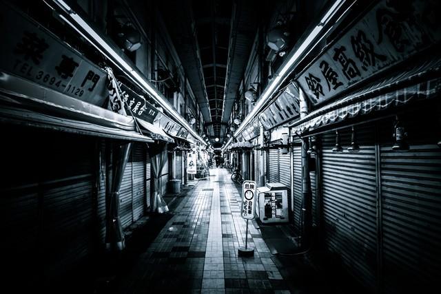 シャッターがおりた商店街とアーケードの写真