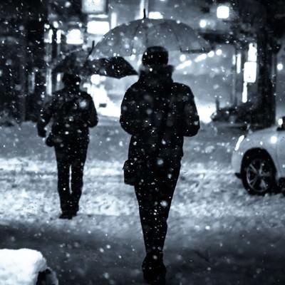 「夜間、舞い散る雪と傘をさす人」の写真素材