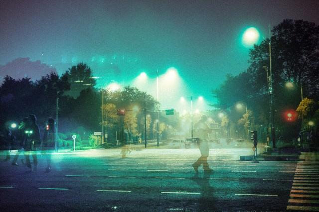 徘徊する人と深夜の街(フォトモンタージュ)の写真