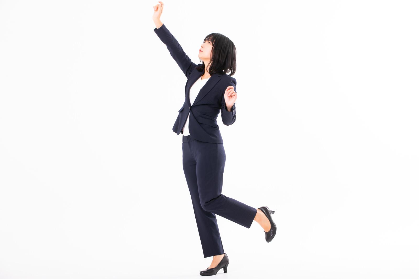 「高い所に手を伸ばす女性社員」の写真[モデル:にゃるる]
