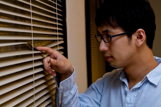 ブラインドから外を覗く男性の写真