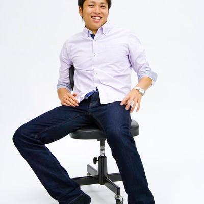 「椅子に座って笑う男性」の写真素材