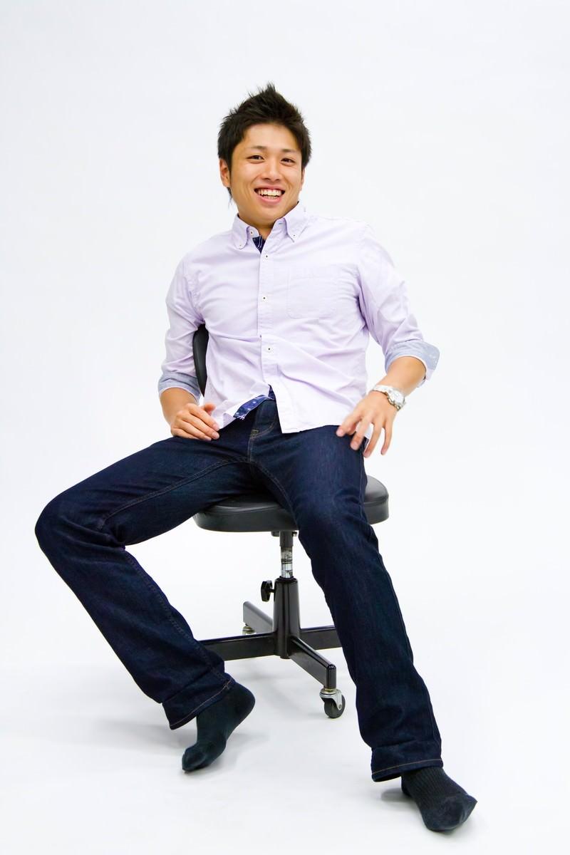 「椅子に座って笑う男性」の写真[モデル:恭平]