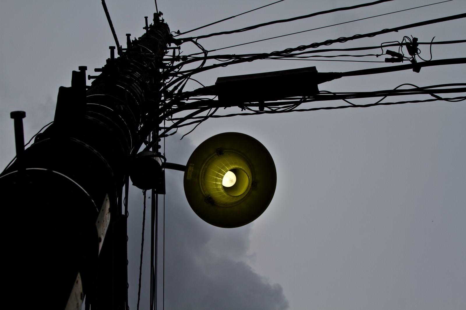 「暗い曇り空と古い電灯」の写真