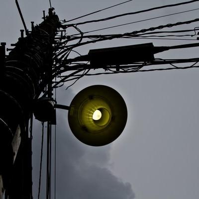 「暗い曇り空と古い電灯」の写真素材