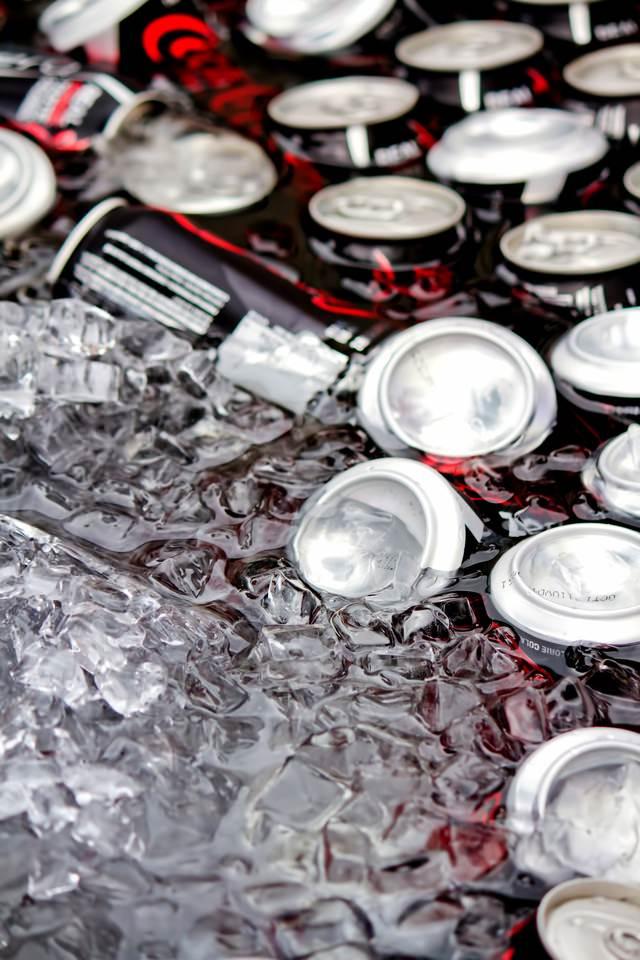 氷水の中で冷えた缶ジュースの写真