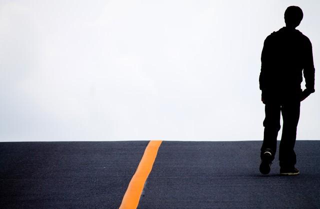 アスファルトを歩く男性の写真