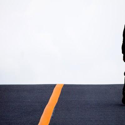 「アスファルトを歩く男性」の写真素材